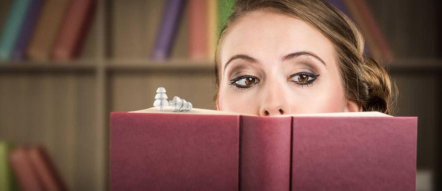Frau schaut hinter einem Buch hervor, auf dem Ohrstöpsel liegen